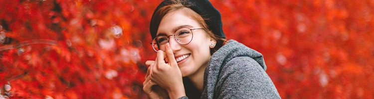 woman wearing glasses smiling by tree